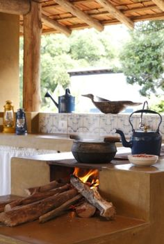 No projeto da designer Vilma Meirelles, o fogão à lenha está posicionado junto à pia, que também leva acabamento de cimento queimado e frontão azulejado.  Fotografia: Evelyn Müller/ Divulgação.