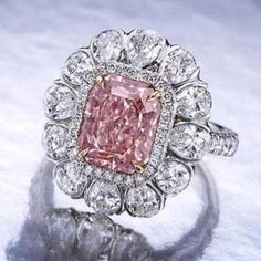 A fancy colored diamond and diamond ring set with a cut-cornered rectangular-cut fancy intense pink diamond, weighing 3.56 carats, within a pear-shaped diamond surround, further enhanced by pavé-set diamond surround, gallery and shoulders