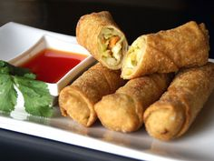 luxurious eggrolls accompanied by a side of sweet and sour sauce