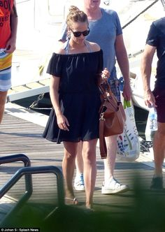 Bardot babe! Kim, 28, flaunted her figure in a bardot black dress as she left the boat...