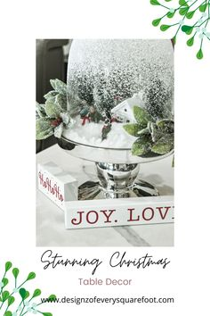 Recreating this stunning snow globe centerpiece is actually quite easy. With some Christmas figurines, faux snow, and a glass vase and pedestal you will have a completed look!! #christmas #christmasdecor #christmasdecorideas #christmasinspo #diychristmasdecor #diychristmasdecorideas #christmasideas #christmastabledecorideas