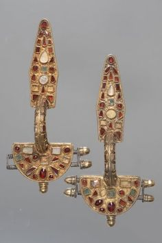 Pair of Fibulae from the migration period - c. 400 AD.  They are of roman fabrication but showing influence of the east German style.  They are made of silvercovered with gold foil and edged with beaded gold wire. The surface was decorated with variously coloured inlays (semiprecious stones, primarily garnets,some convex, some cut flat, as well as glass and enamel). Between them are tinygold granules soldered to the surface in groups of three