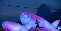 Silhouette of man running near fish-shaped sculpture made of plastic bottles on the beach of Botafogo in Rio de Janeiro - Felipe Dana / AP