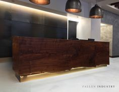 Waterfall reception desk in residential Tribeca lobby. Made from a signle claro walnut cut. LEDs highlight the live edge.  Live edge custom built modern furniture and architectural elements made from reclaimed wood and fallen trees by Fallen Industry. Fallen Industry is a home and office design studio based in NYC Brooklyn. Created by New York sculptor and designer Paul Kruger.