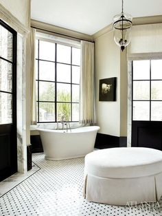 Grand and luminous black and white bathroom, with high ceilings, checkered floor tiles and generous natural light.