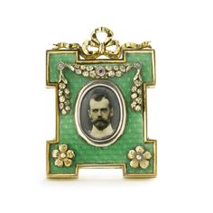 A Russian gem-set gilded silver and transparent enamel photograph frame, retailed by Fabergé, St. Petersburg, 1898-1908 shaped rectangular, the surface enameled translucent green over a wavy guilloché ground, applied with gilt swags and flowerheads set with diamonds and rubies, surmounted by a bowknot, with ivorine back and shaped strut, with unidentified Cyrillic maker's mark PE or PF, Fabergé in Cyrillic.