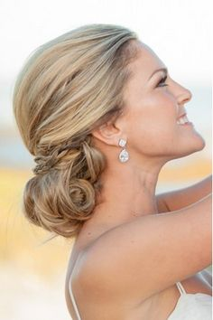 A low chignon with a delicate braid wrap is a chic and stylish wedding hairstyle.