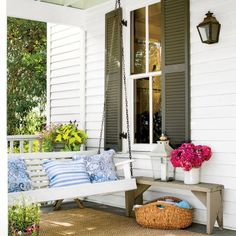 Classic White Porch Swing: A traditional wooden porch swing is cozied up with blue-and-white cotton pillows from HomeGoods. A rustic bench serves as a side table.