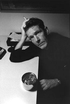 John Cage smokes a cigarette.
