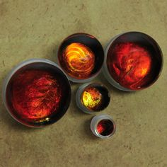 These glass plugs are made of clear glass with a metallic mix of red, orange, and yellow colored glass added...