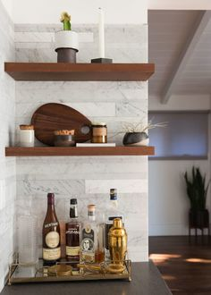Detail of open shelving in modern farmhouse kitchen with striated marble backsplash, wood shelves, and rustic accessories. Home is California bungalow of Brendon Urie (Panic at the Disco). Design by Ashley Drost.