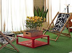 Na varanda, cadeiras de praia e mesa de centro com obra do artista jardineiro André Feliciano. As câmeras lembram girassóis
