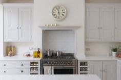 Sustainable Kitchens - Bright Open Plan Family Kitchen in London. Oak shaker style cabinetry painted in Farrow & Ball Ammonite with built in spice racks on either side of the Smeg range cooker. Next to the cabinetry is a decorative ladder. The worktop is Bianco Fantasia. The extractor is housed in the chimney breast and has a cornice style shelf for decorative items.