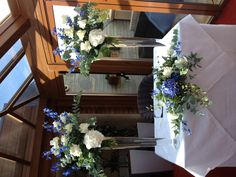 Blue delphiniums and white hydrangeas with gardenia avalanche roses. Tall vases have a big impact. A x