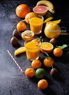 Citrus Fruit - Variety of citrus tropical fruit with a glass of orange juice with a paper straw: Tangerines, grapefruit, lime, oranges and banana. Copy Space