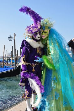~A Venetian couple poses in costume with gondolas and the canal as a backdrop~