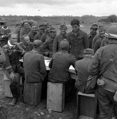 German soldiers, captured by Allied Armies on the Normandy beachheads on June 16, 1944, are checked by fellow prisoners. (AP Photo/Jack Rice)