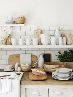 Smooth wood and white porcelain against white subway tiles on open shelving. A classic look with a touch of rustic style.