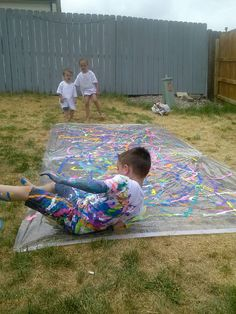 """Paint slip n slide! Buy a clear tarp or even two clear shower curtains ( that's what we did ) stake them into the ground. Squirt paint all over and have fun! You may want to add a little water just to help make it """"slippery"""". We also bought the kids white t-shirts so when they went down they would paint their shirts !"""