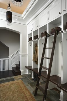 Fabulous mudroom features a row of shelves filled with seagrass bins stacked over open lockers lined with wood ladders on rails.