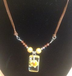 Glass bead with a pressed flower inside is set with Swarovski bi one beads and miracle beads on a brown suede cord. £10