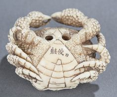 """A Japanese ivory crab netsuke. 19th century, Flat form with bumpy skin, signed on the bottom near the himotoshi. 1 3/4""""."""