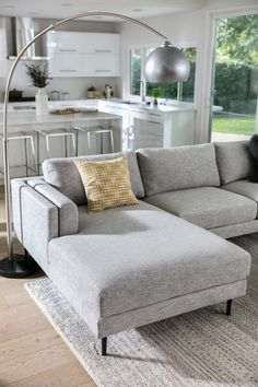Mid-century style light grey sectional sofa. From lean and lofty tapered legs, to a squared-off silhouette, to inner arm cushions that add extra sophistication, this design is poised to become the best spot in your home. Not to mention, the Aquarius Sectional is covered in a light grey fabric that's both textured and tailored. #WestsideLoft #LivingSpaces