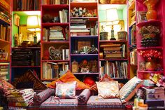 Zandra Rhodes' wacky house. I love how these shelves are crammed with beloved books and objects, and love the use of the lamps.