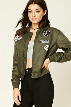 A woven bomber jacket featuring ribbed trim, zip-up front, two front slanted pockets, long sleeves, and various patches in different designs. Patched Bomber Jacket $39.90