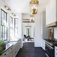 Black and White Galley Style Kitchen with Mercury Glass Pendants