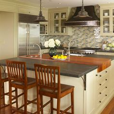Cream cabinetry, slate countertop, wood floors.