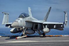 """A Boeing F/A-18F Super Hornet, from Strike Fighter Squadron 41 (VFA-41) """"Black Aces,"""" resting on the flight deck of the USS John C. Stennis (CVN 74)."""