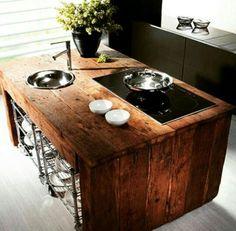 cucina ad isola realizzata con assi di legno di recupero, piano cottura ad induzione e lavello a ciotola con rubinetto soprapiano