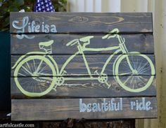 """Reclaimed wood sign with a hand-painted vintage style tandem bicycle with the saying """"Life is a beautiful ride""""."""