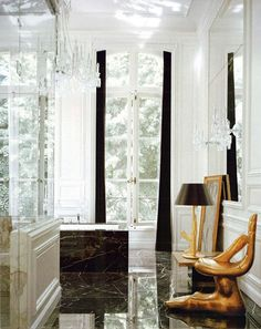 Lenny Kravitz bathroom, black granite, white, gold hand chair