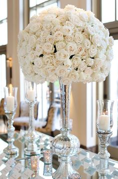 This striking arrangement contains white roses in a silver floral vessel for a sophisticated touch.