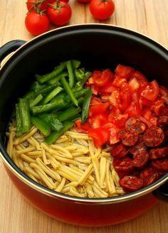 Dans une casserole, versez 4 dl d'eau avec 1 cs d'huile d'olive, puis mettez 2 tomates moyennes coupées en dés, et un poivron rouge en lamelles, avec un chorizo en rondelles sans peau, et 200 g de pâtes type penne, casarecce ou troffie. Faites bouillir puis laisser cuire encore 10 min en remuant souvent.