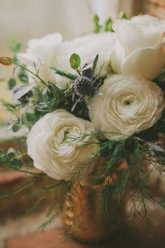 Floral inspiration: white ranunculus, white spray roses, seasonal greenery, and blue thistles