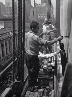 A young woman's likeness is painted on a billboard advertising New York 1947