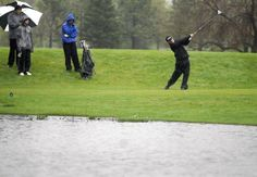 A golfer hits a tee-shot in the heavy rain and wind during the Bismarck High School Invitational Golf meet held at Tom O'Leary Golf Course. Standing water in the foreground covers a low-lying area on the course. MIKE McCLEARY/Bismarck Tribune