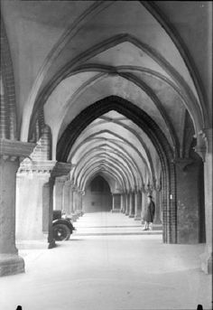 Woman standing under archway, Lübeck, Germany by Martin Munkácsi