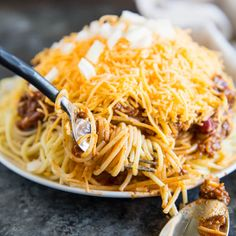 A photo of a plate if Cincinnati Chili topped spaghetti, garnished with white onion and shredded cheddar cheese. There is a fork swirling the spaghetti in the foreground. There is a white linen napkin in the background, and the plate is on a dark blue counter top.