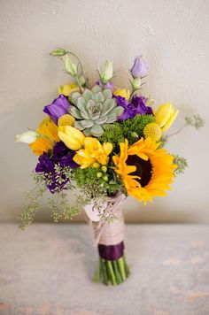 A beautiful hand-tied bouquet of sunflowers, purple lisianthus, yellow tulips and succulents.
