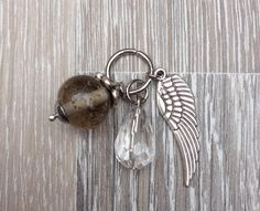 Bedel van bergkristal druppel, 12mm grijze glas kraal met kraalkap en een metalen vleugel. Te koop bij JuudsBoetiek voor €3,00. Wil je er een ketting bij? Vraag naar de mogelijkheden! Bestellen kan via juudsboetiek@gmail.com.