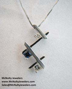 A contemporary spin on a past, present, and future pendant. Made in white gold with princess cut sapphire and diamonds.  McNulty Jewelers original design