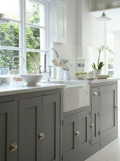 For a modern farmhouse feel, an unconventional cabinet color, like this grey, paired with industrial style hardware gives this kitchen a stylish edge.