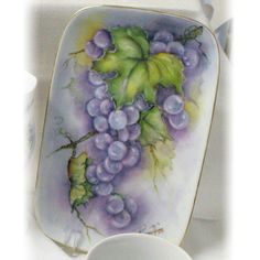 """Rosemary's Porcelain Art Hand Painted Rectangular Tray with Grape Design: This rectangular tray has an original design of luscious grapes painted at a time when Rosemary's grapes were ripening on the acreage where she lives. It makes a great piece to serve cookies on or to use decorating your home. Hand painted by Nebraska artist Rosemary Thomas of Rosemary's Porcelain Art located in Milford, NE. signed by the artist. May be personalized. Plate is 5.5"""" by 8.5"""". #GrowNE"""