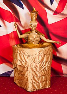 Human Torch Living Table - this Human table has the Olympic flame in her head dress and is all gold.