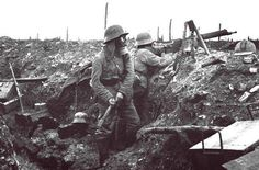 """historicaltimes: """" German troops in the trenches near Verdun. The soldier prepares to throw a grenade. While a machine gunner scans no man's land, 1916 """""""