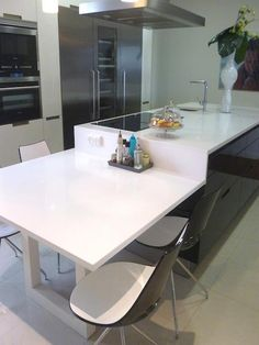 #Cocina combinada en negro y blanco con isla central como zona de trabajo y de mesa integrada. #Cocinadediseño realizada en SANTOS modelo minos lacado alto brillo, la Encimera en #Silestone Blanco Zeus.